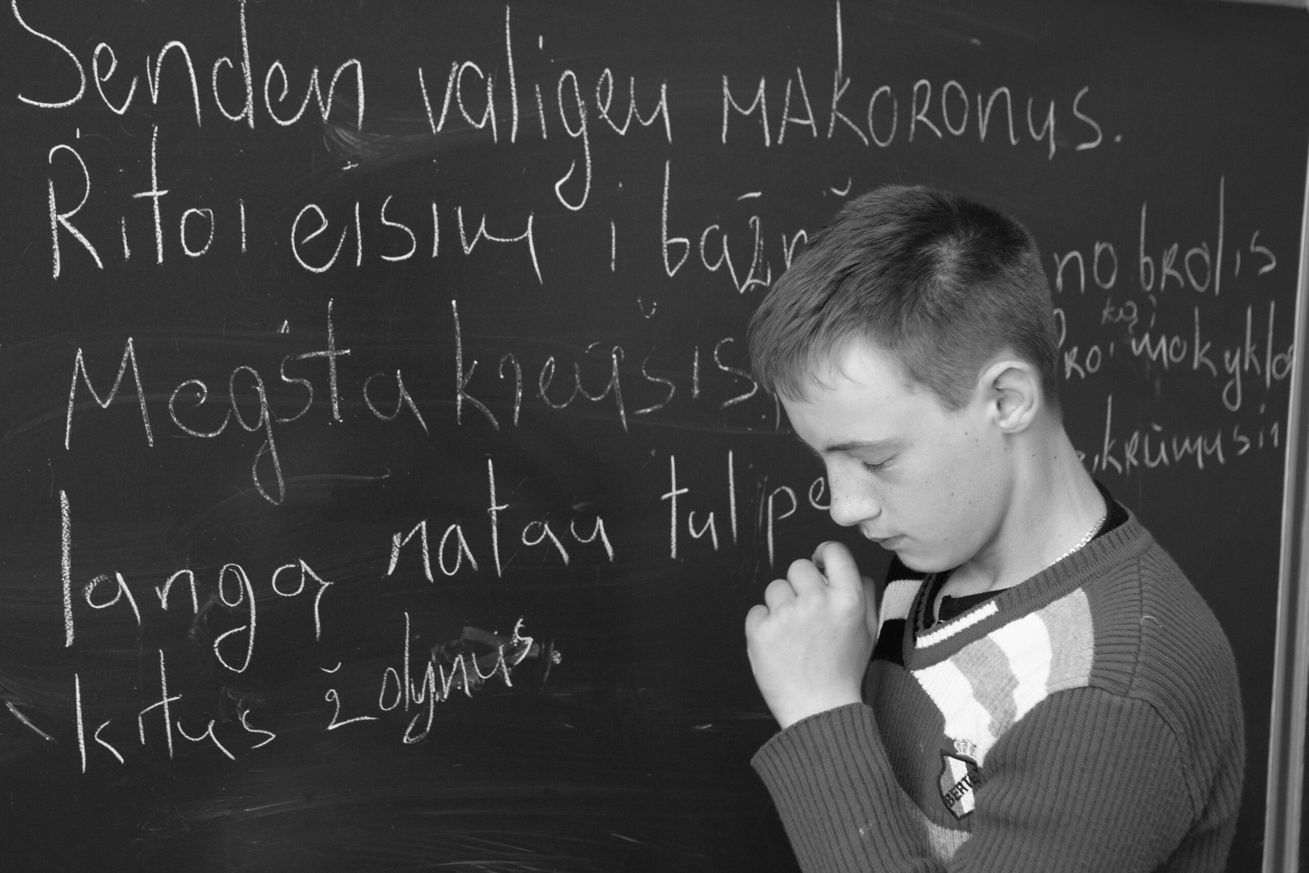 Mokinys prie lentos.