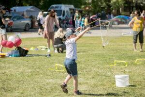 Vaikas žaidžia pievoje