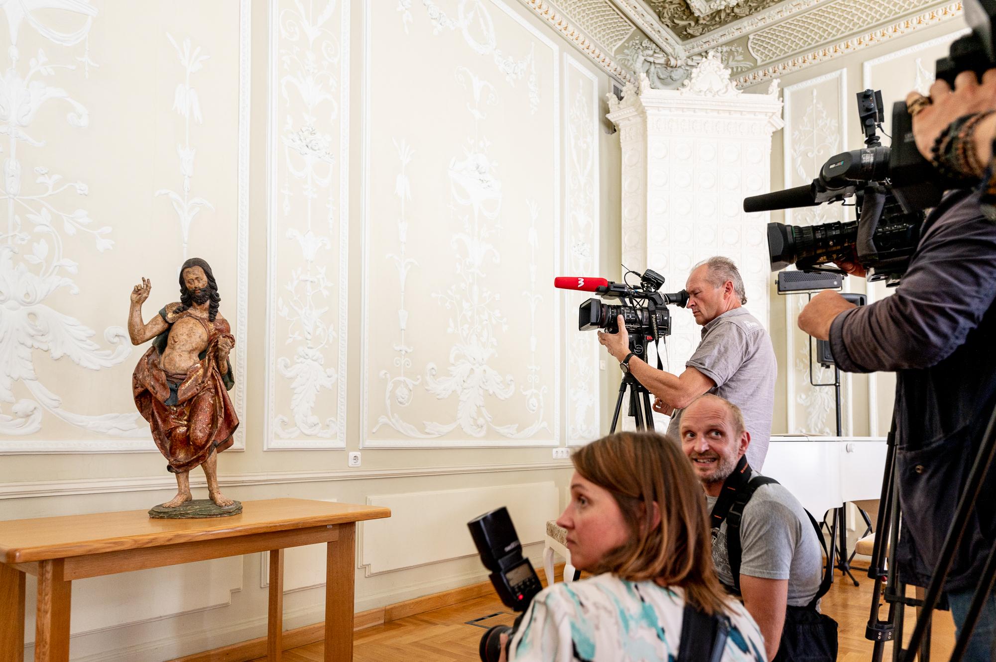 Skulptūra stovi ant stalo, fotografai fotografuoja.