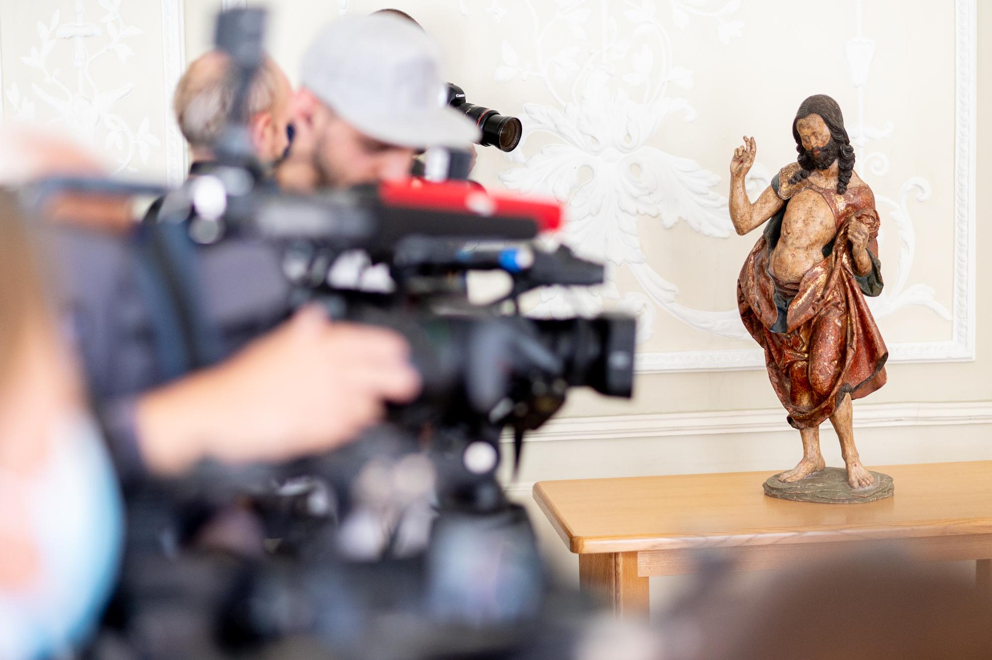 Skulptūra stovi ant stalo.