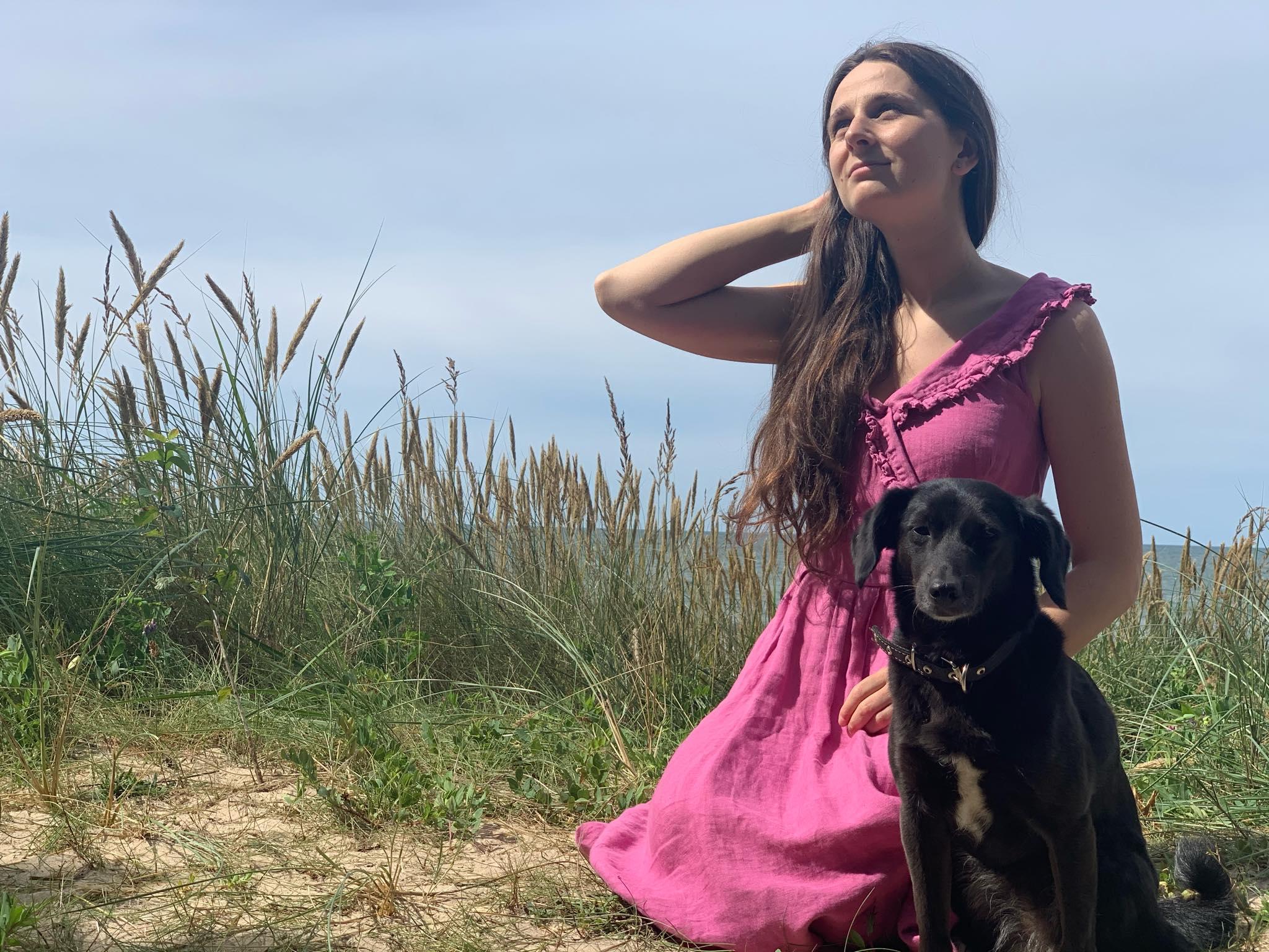 Mergina su juodu šuniuku kopose, už nugaros matosi jūra.
