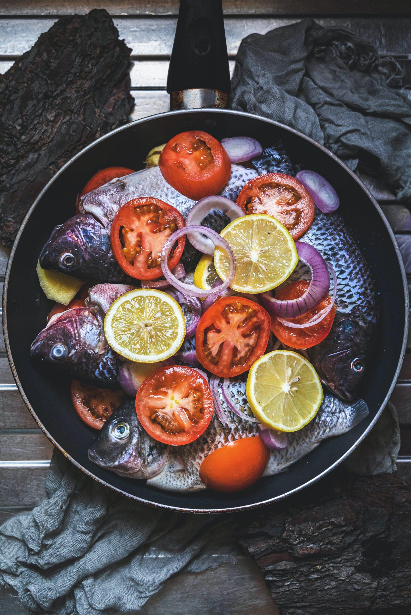 Žuvis keptuvėje su daržovėmis.