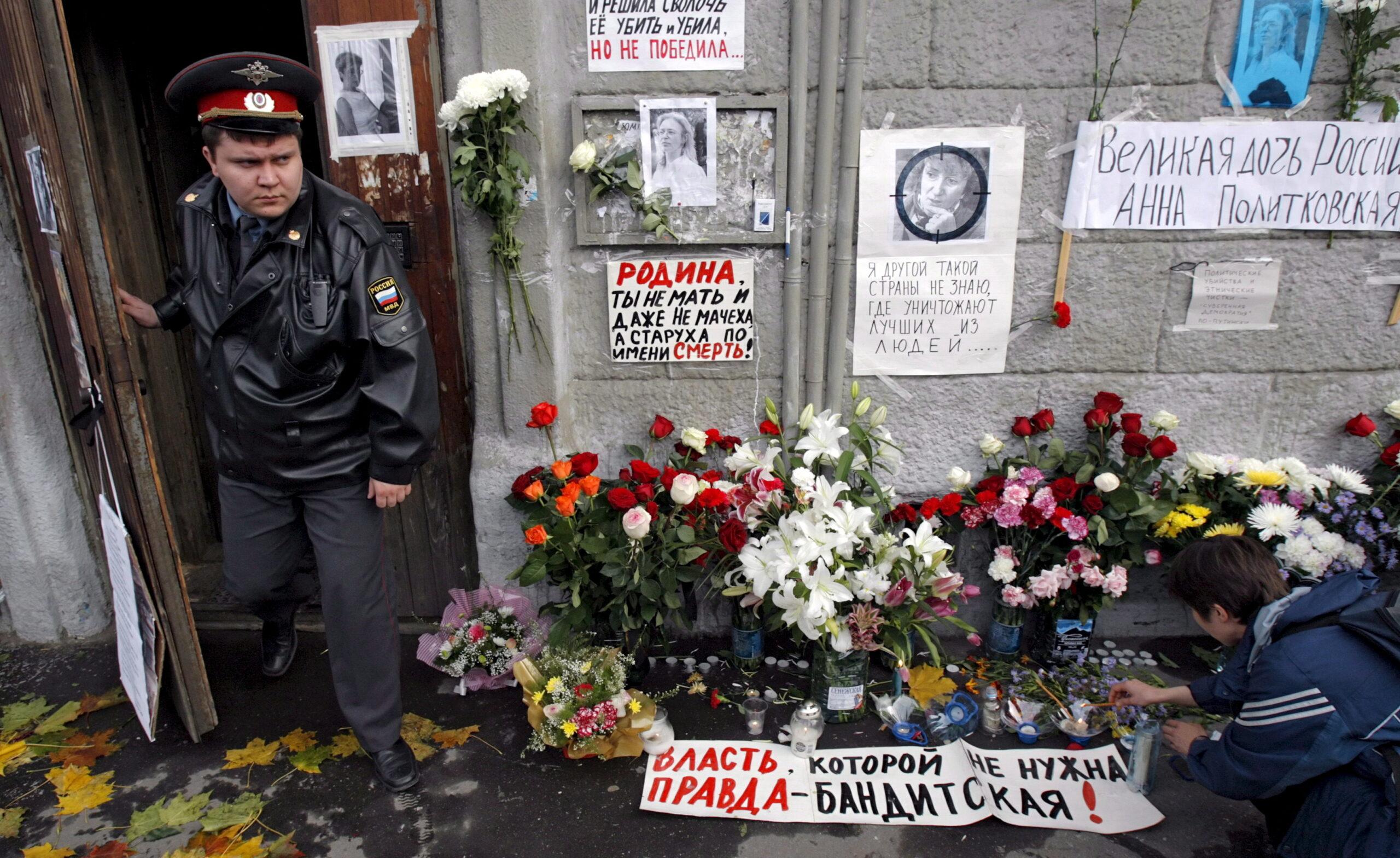 Gėlės prie namo sienos ir milicininkas.
