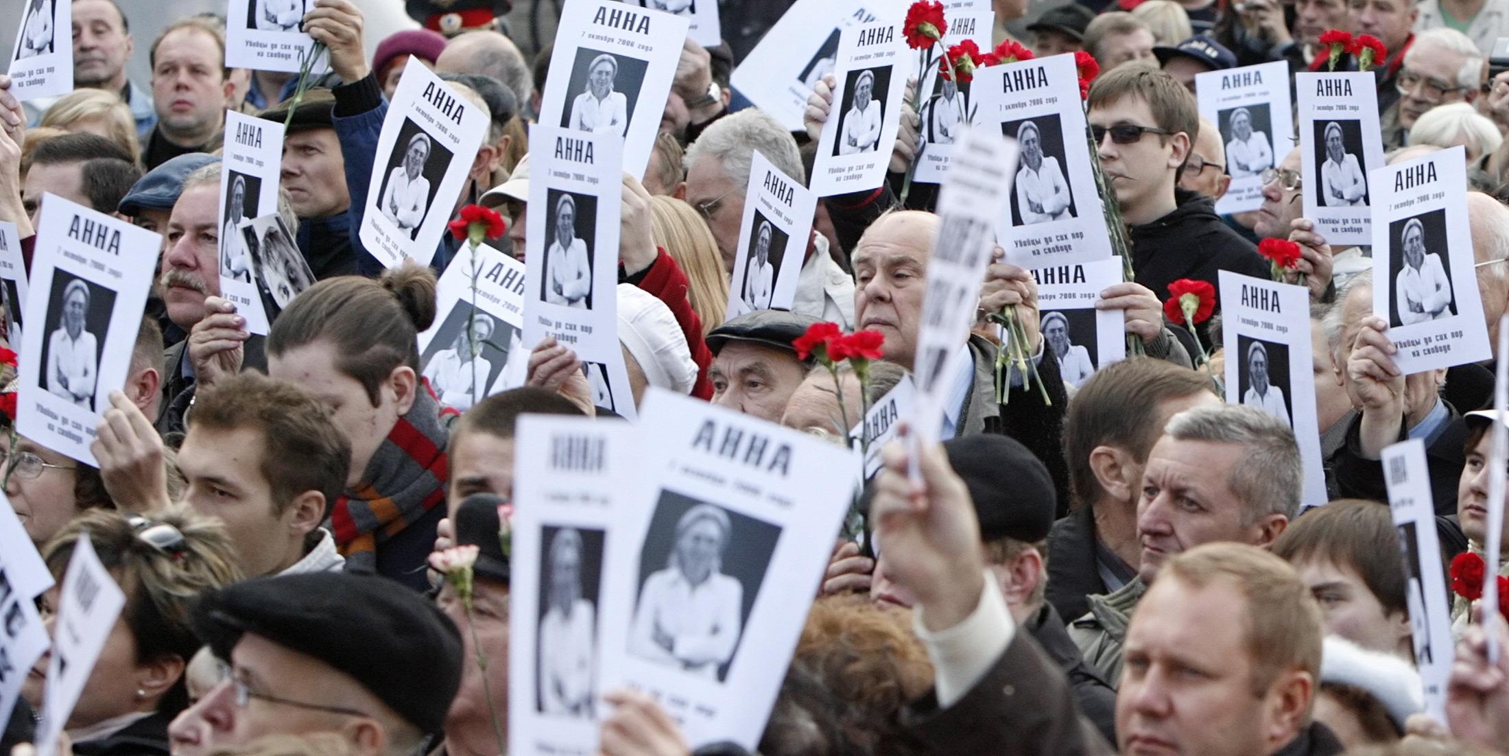 Žmonės su plakatais rankose.