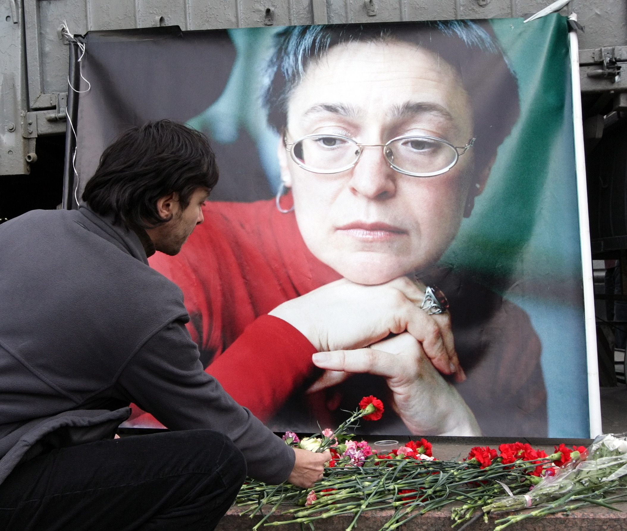 Žmogus deda gėles prie nužudytos žurnalistės portreto.