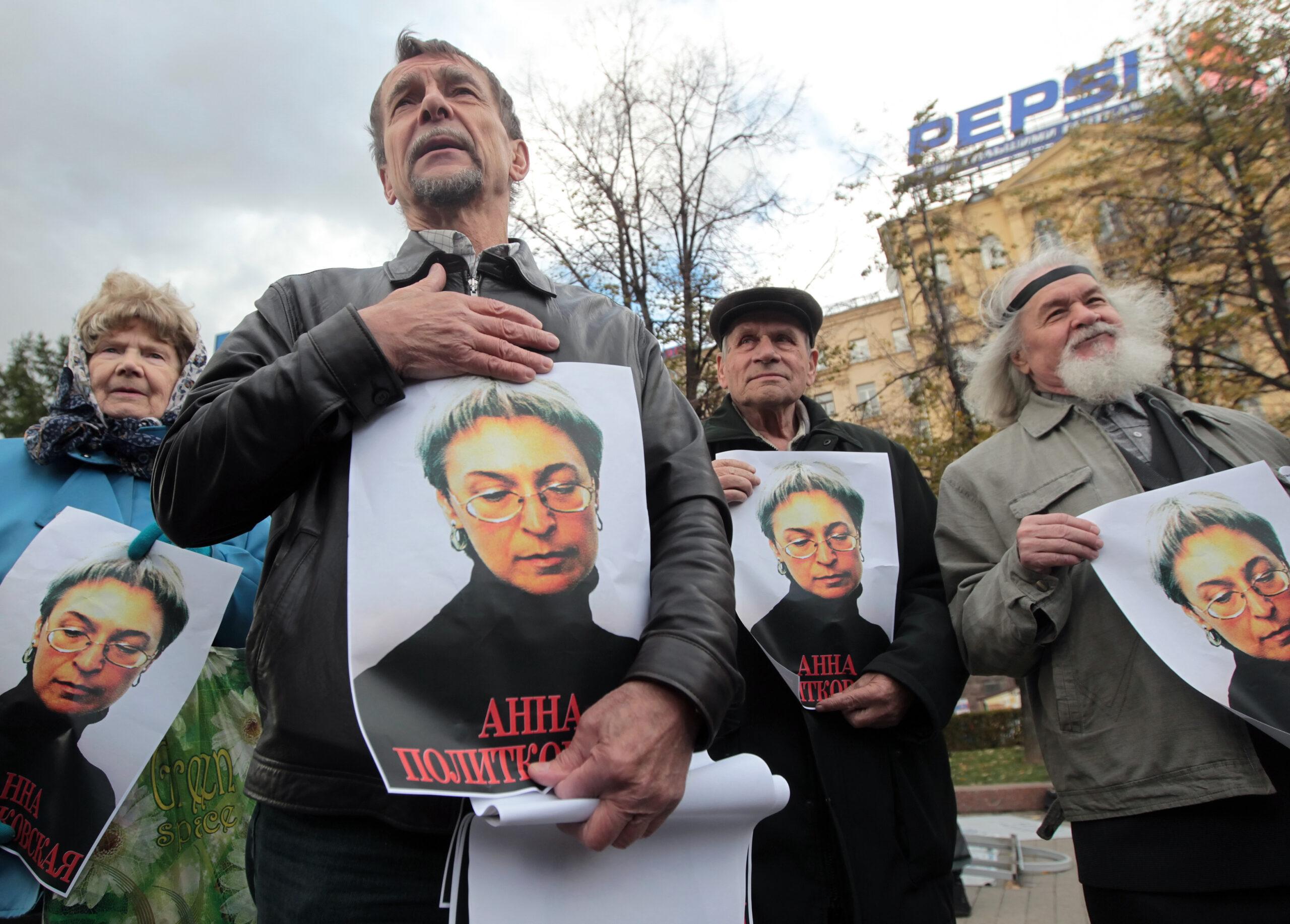 Žmonės su nužudytos žurnalistės portretais rankose.