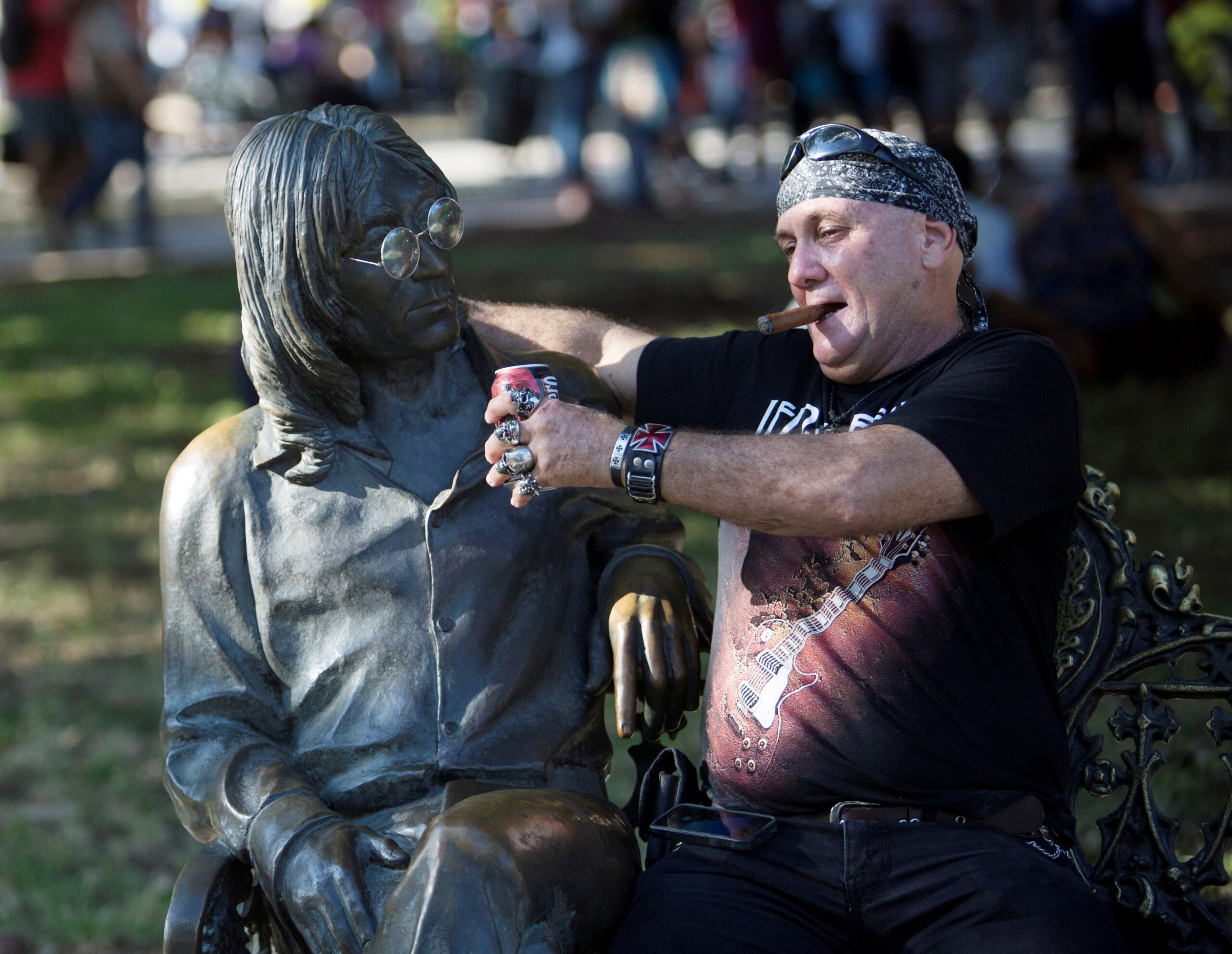 Rūko cigarą, geria alų, apkabinęs skulptūrą.