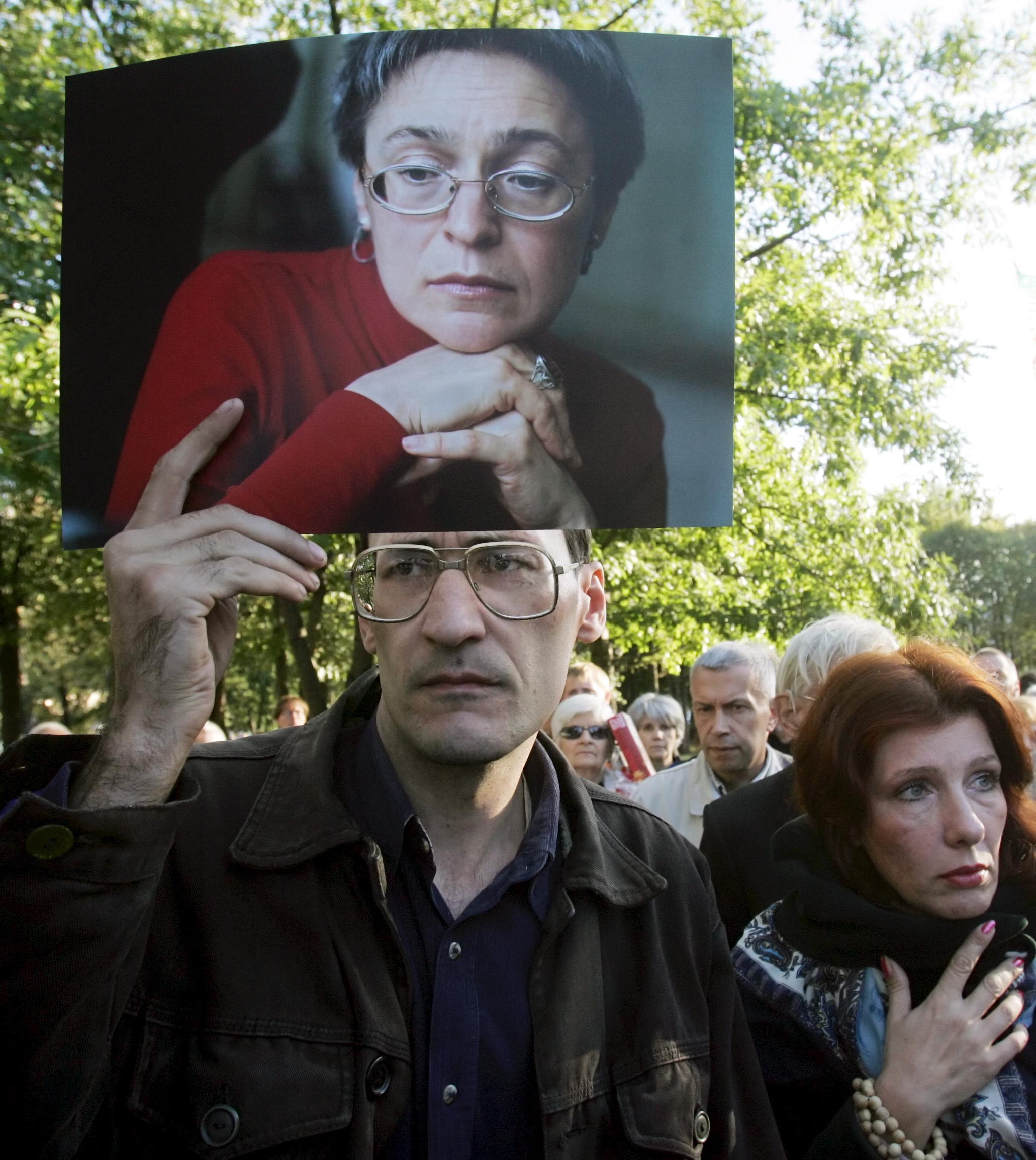Žmogus su nužudytos žurnalistės nuotrauka rankose.