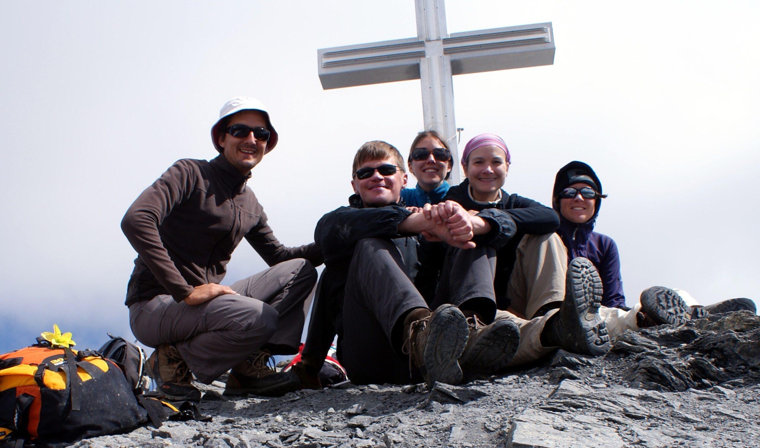 Ant kalno penki žmonės susėdę.