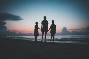 Papludimyje leidžiasi saulė, matosi žmonių šešėliai
