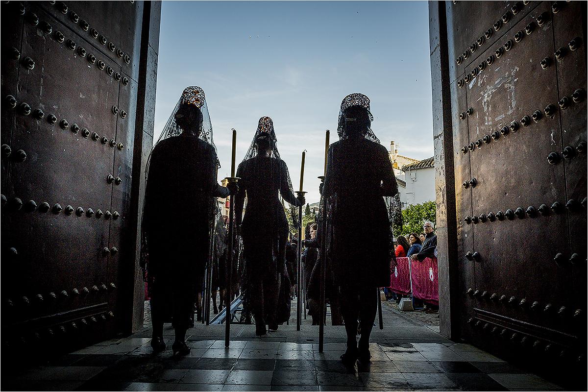Trys moterys su gedulo mantilijomis bažnyčios prieangyje.