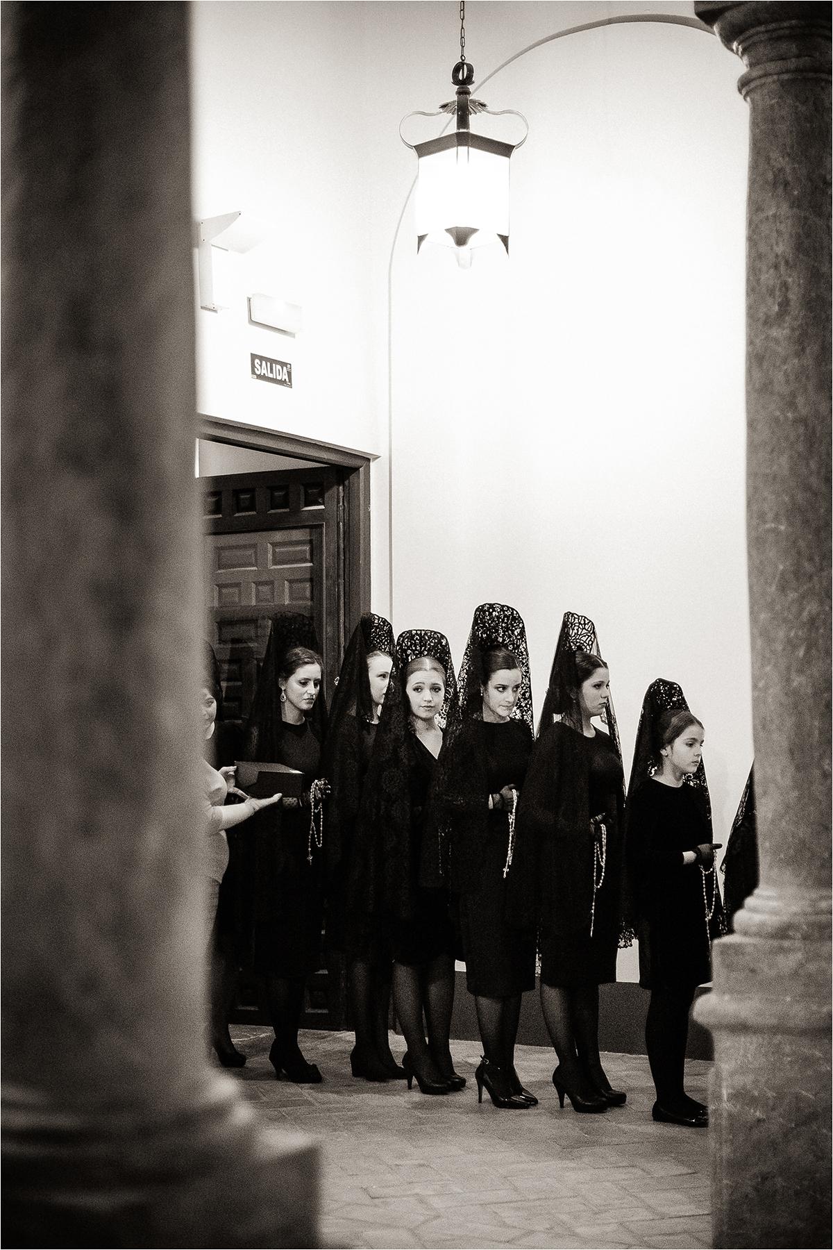 Gedulinėmis mantilijomis pasipuošusios merginos prie bažnyčios.