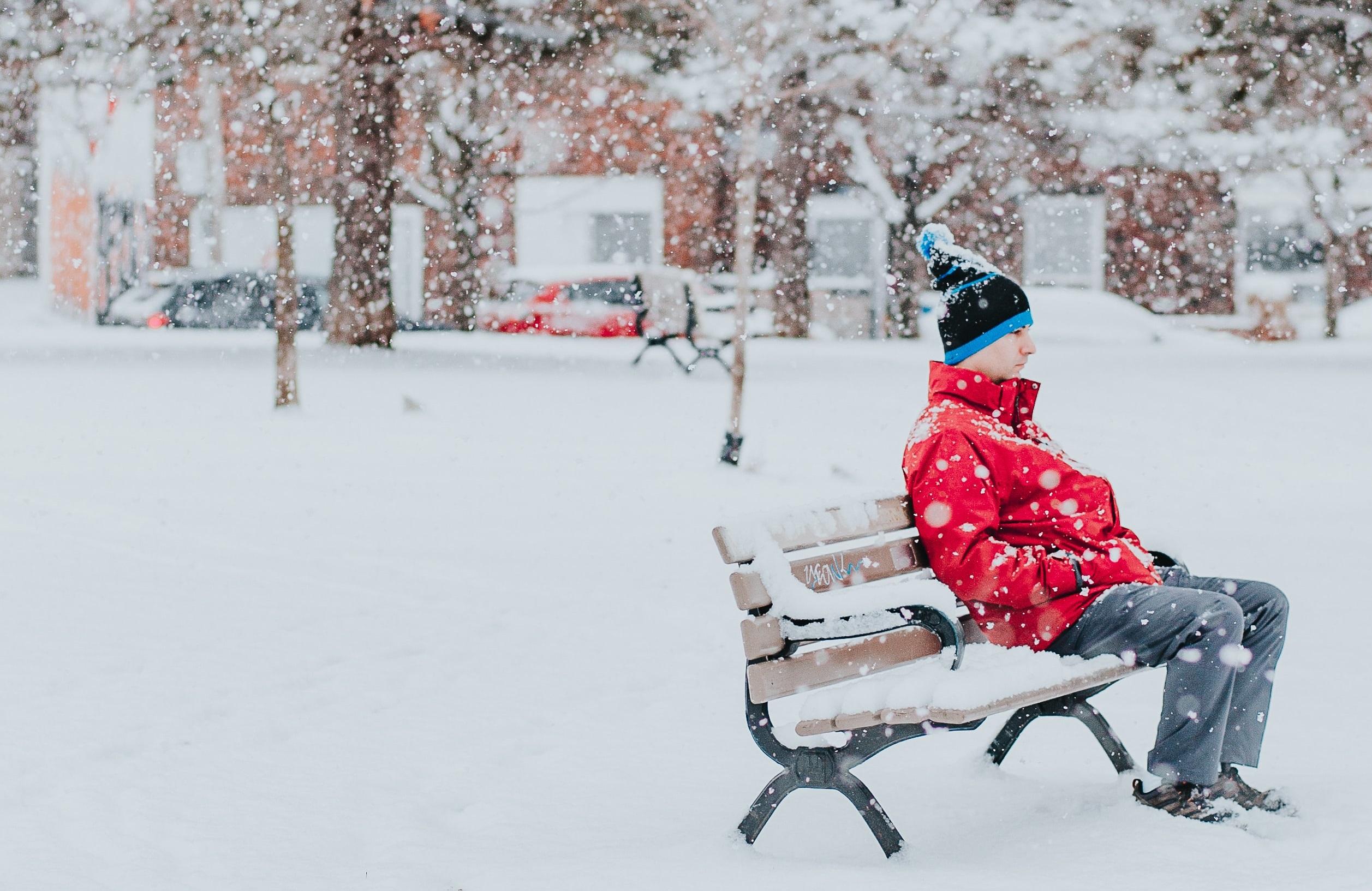 Vyras sėdi ant suoliuko žiemą