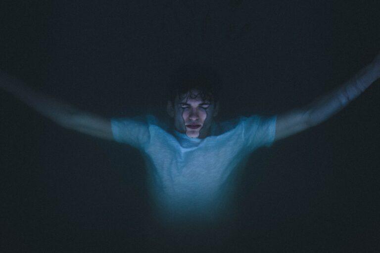 Vaikas tamsoje atsirėmęs į stiklą