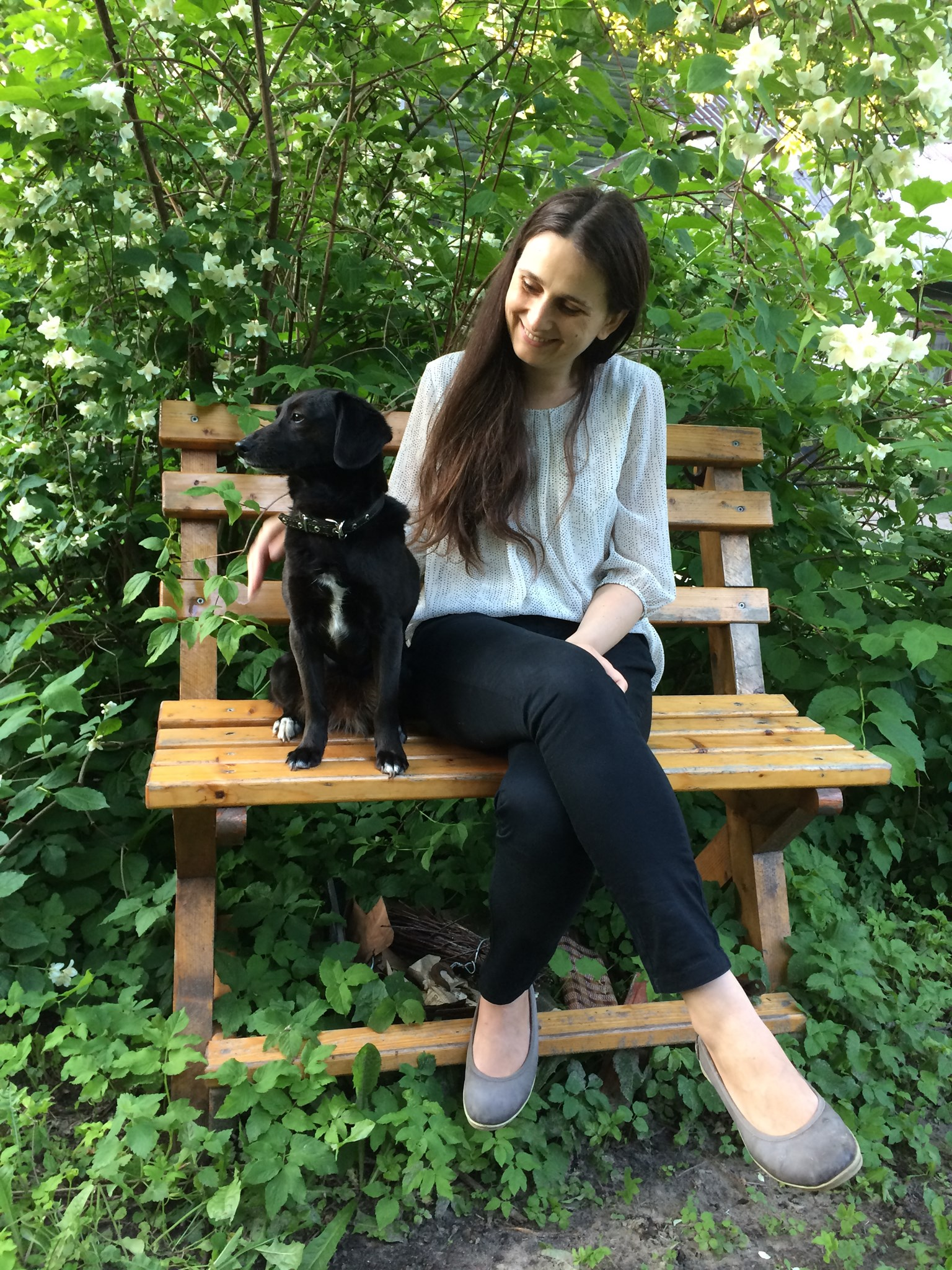 Ant suoliuko sėdi mergina su mažu juodu šuniuku