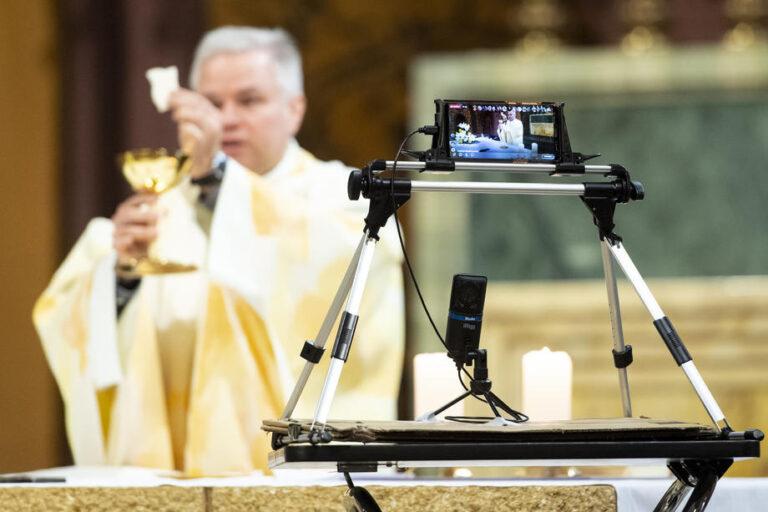 Kunigas aukoja Mišias ir jį filmuoja telefonas.