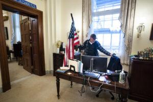 Įsilaužėlis su Amerikos vėliava politikės Nancy Pelosi kabinete