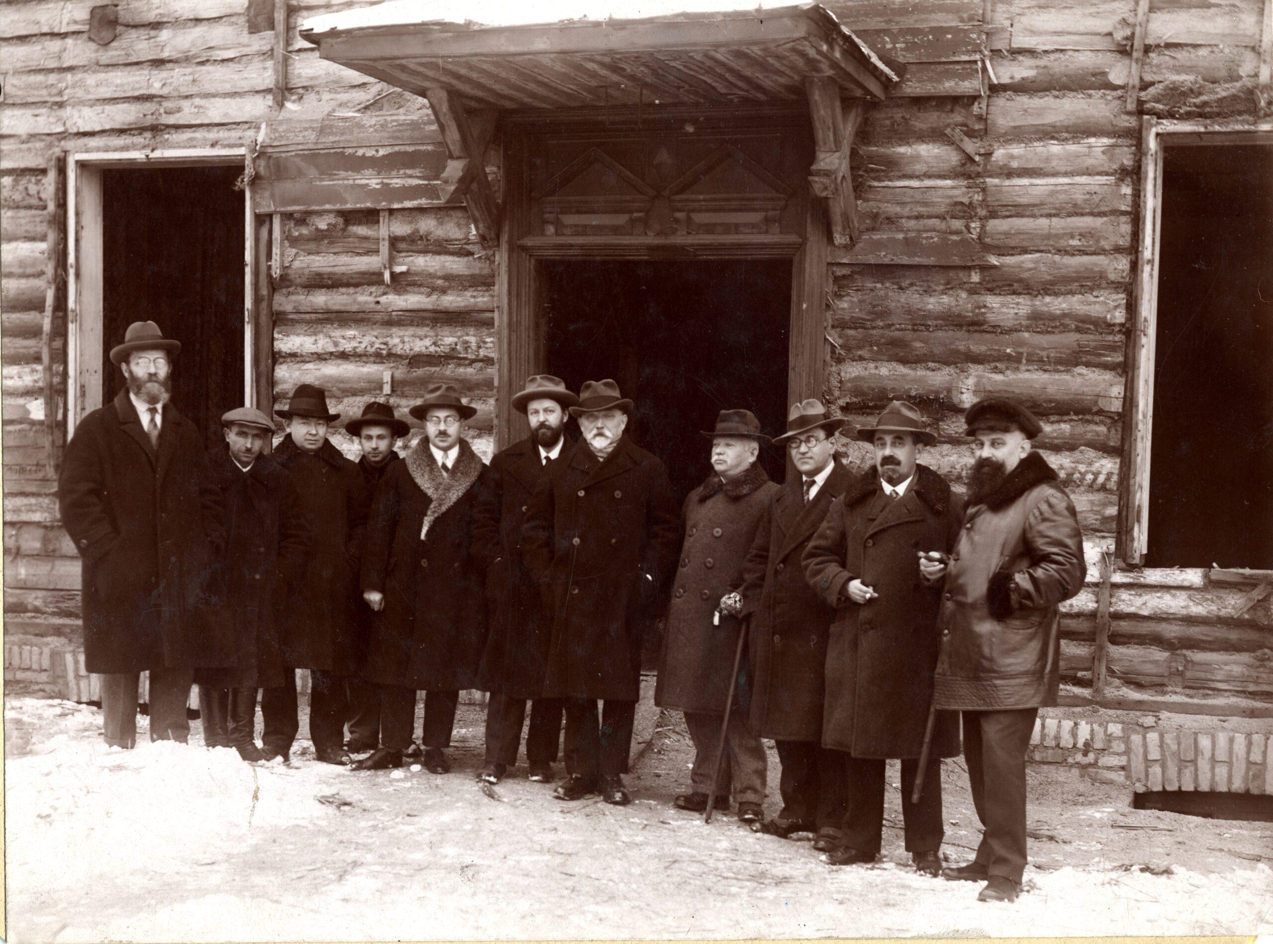 Grupelė žmonių prie medinio pastato.